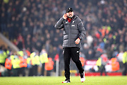 A happy Liverpool Manager Jurgen Klopp listens to the Kop singing during the Premier League match between Liverpool and Manchester United at Anfield, Liverpool, England on 19 January 2020.