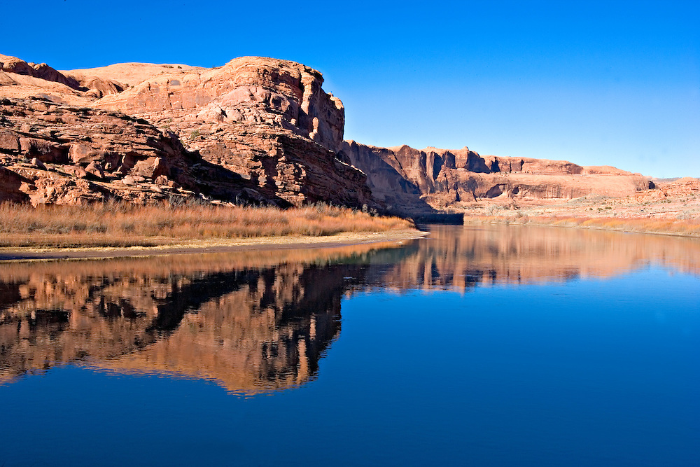 redrock cliffs reflecting in placid Colorado River, Utah
