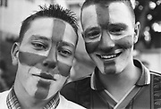 Two football fans with England colours painted on their faces