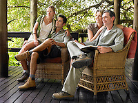 Two couples sitting on terrace smiling one holding book