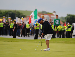 Pictured: Golfers continue playing despite protesters gather to protest against US Presidential candidate Donald Trump as he arrives in Scotland to open his multi-million pound redevelopment of his Turnberry hotel and golf resort.<br /> <br /> <br /> &copy; Dave Johnston/ EEm