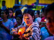 19 OCTOBER 2018 - BANGKOK, THAILAND: A woman goes into a trance with candles during Navratri observances in Bangkok. Navratri is a nine night (10 day) long Hindu celebration that marks the end of the monsoon and honors of the divine feminine Devi (Durga). The festival is celebrated differently in different parts of India, but the common theme is the battle and victory of Good over Evil based on a regionally famous epic or legend such as the Ramayana or the Devi Mahatmya. Navratri is celebrated throughout Southeast Asia in communities that have a large Hindu population. Because Navratri honors the feminine Devi, Navratri is especially popular with Thai women and transgendered people.  PHOTO BY JACK KURTZ