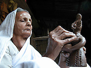 "An unidentified octogenarian woman is busy to give dry-shape-design on the world famous ""Terracotta"" doll at Asharikandi, about 291 kilometres southwest of Guwahati, capital of North-Eastern Indian State of Assam..Including national and international award winner, more than 80% families are engaged in this ethnic-art (handicraft) and pass their life after sell these Terracotta product in the national and international market, while the Government has declared this village as a model village. ( Photo/Shib Shankar Chatterjee)."