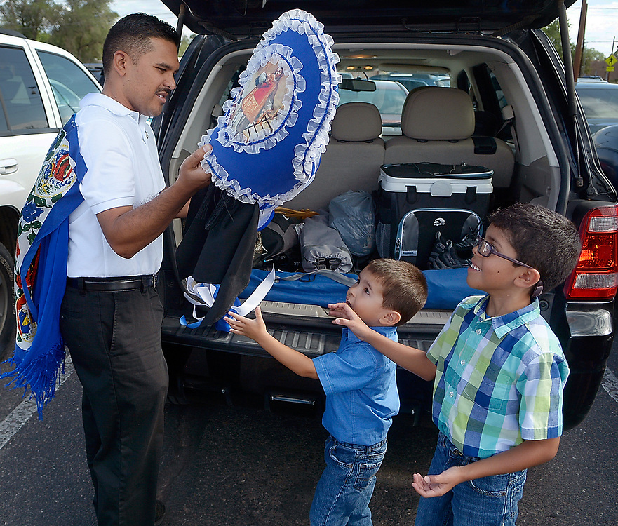 gbs081017f/RIO-WEST -- Tim Lucero hands his cupil to his sons Aiden, 4, and Brandon, 6, to carry into Our Lady of Sorrows Catholic Church during Las Fiestas de San Lorenzo on Thursday, August 10, 2017.(Greg Sorber/Albuquerque Journal)