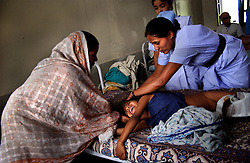 KATHMANDU, NEPAL, APRIL 14, 2004: Nepali nurses look after Sunil Sharma, 9 years old, in a hospital in Nepalganj, Nepal who was injured in an explosion 10 days earlier by Maoist insurgents fighting government forces April 14, 2004.   (Ami Vitale/Getty Images)