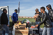 Mineo, Sicily, Italy, April 2015<br /> In the region of Catania, Sicily, lies the biggest center for asylum seekers in Europe, &quot;CARA&quot; (Centro di Accoglienza per Richiedenti Asilo), near the village of Mineo. Over four thousand migrants live in this ancient village built initially to host families of US army soldiers, from a military base nearby. The center is built like a real village with its health center, nursery, administrative buildings, dining hall, stadium ... After what is often a dreadful crossing of the Mediterranean Sea, the survivors have to wait up to fifteen months to obtain a possible residence permit. A street seller is selling fruit and vegetables to migrants from central CARA Mineo. &copy; Jean-Patrick Di Silvestro