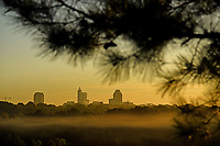 The Raleigh skyline glows warm at sunrise as a low morning fog floats over Lonnie Poole Golf Course on Centennial Campus.
