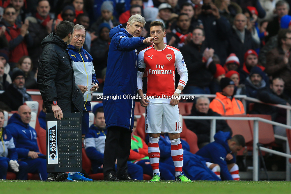 11 January 2015 - Barclays Premier League - Arsenal v Stoke City - Arsene Wenger, Manager of Arsenal passes instructions to Mesut Ozil on his return from injury - Photo: Marc Atkins / Offside.