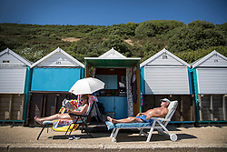 © Licensed to London News Pictures. 26/06/2018. Bournemouth, UK. A couple relax in front of their beach hut in hot afternoon sunshine at Bournemouth. Most of the UK is enjoying summer temperatures in the high 20's today. Photo credit: Peter Macdiarmid/LNP