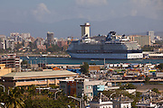 Cruise ship with the skyline of San Juan in San Juan, Puerto Rico.