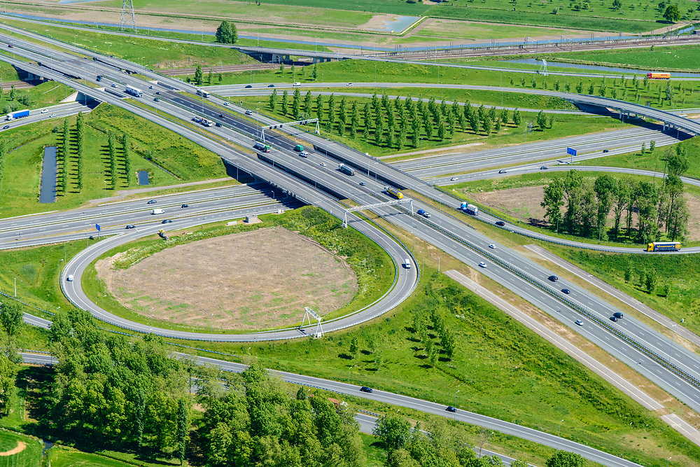 Nederland, Gelderland, Over-Betuwe, 13-05-2019; knooppunt Valburg. Kruising A50 en A15 (vlnr), infrabundel met Betuweroute (bovenkant verkeersplein)<br /> Valburg junction. Junction A50 and A15, infrastructure bundle with Betuwe Route.<br /> <br /> luchtfoto (toeslag op standard tarieven);<br /> aerial photo (additional fee required);<br /> copyright foto/photo Siebe Swart