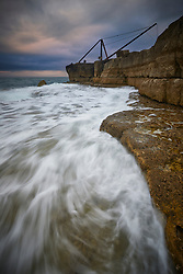 The Old Red Crane at Portland Bill in Dorset is a relic of the stone quarrying that happened all around the island coast. Photographed in evening light under a stormy sky, with ocean waves breaking over rock ledges in the foreground.