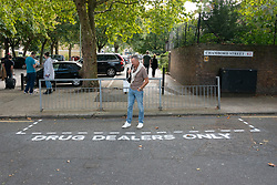 "© Licensed to London News Pictures. 16/09/2018. London, UK. Tourists pose next to community activists spray paint ""Drug Dealer Only"" parking spaces and erect street signs to highlight increasing levels of drug dealing in the E2 postcode, known as the cheapest heroin in Europe, East London, UK. Photo credit: Ray Tang/LNP"
