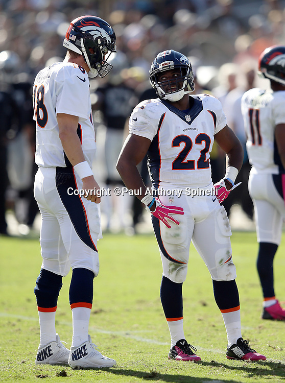 Denver Broncos running back C.J. Anderson (22) runs the ball talks to Denver Broncos quarterback Peyton Manning (18) during a break in the action during the 2015 NFL week 5 regular season football game against the Oakland Raiders on Sunday, Oct. 11, 2015 in Oakland, Calif. The Broncos won the game 16-10. (©Paul Anthony Spinelli)