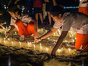 26 DECEMBER 2014 - PATONG, PHUKET, THAILAND: Thai students light candles for victims of the 2004 tsunami on Patong Beach in Patong, Phuket. Hundreds of people died in Patong and nearly 5400 people died on Thailand's Andaman during the 2004 Indian Ocean Tsunami that was spawned by an undersea earthquake off the Indonesian coast on Dec 26, 2004. In Thailand, many of the dead were tourists from Europe. More than 250,000 people were killed throughout the region, from Thailand to Kenya. There are memorial services across the Thai Andaman coast this weekend.    PHOTO BY JACK KURTZ