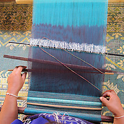 Light Blue, Thailand by Mida<br /> <br /> This is Mida&rsquo;s mother, See Taun, weaving traditional Thai Karen fabric. She is forty-one years old. Weaving is a family tradition. Both Mida and her mother learned to weave when they were eight years old. Weaving is important to Thai Karen culture, and only the women weave.<br /> <br /> Mida is from Mae sa Pok, a Karen village located in the Mae Wang district of Northern Thailand. She spends most of her time in her village where she can be with her son, Warinton. Her mother, Si Taun, and the other women of the village spend most of their time weaving scarves and other items, which can be sold to western tourists. She enjoys taking photos of her village and her family.