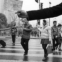 China, Shanghai, Crowd of pedestrians crossing at street crosswalk on rainy winter afternoon