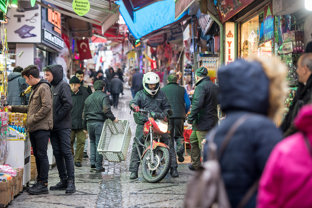 Shoppers browse goods for sale along busy narrow street of outdoor marketplace as a man with a motorcycle tries to make his way through, Istanbul, Turkey