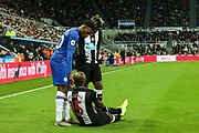 Callum Hudson-Odoi (#20) of Chelsea and Allan Saint-Maximin (#10) of Newcastle United check on the injured Jetro Willems (#15) of Newcastle United during the Premier League match between Newcastle United and Chelsea at St. James's Park, Newcastle, England on 18 January 2020.