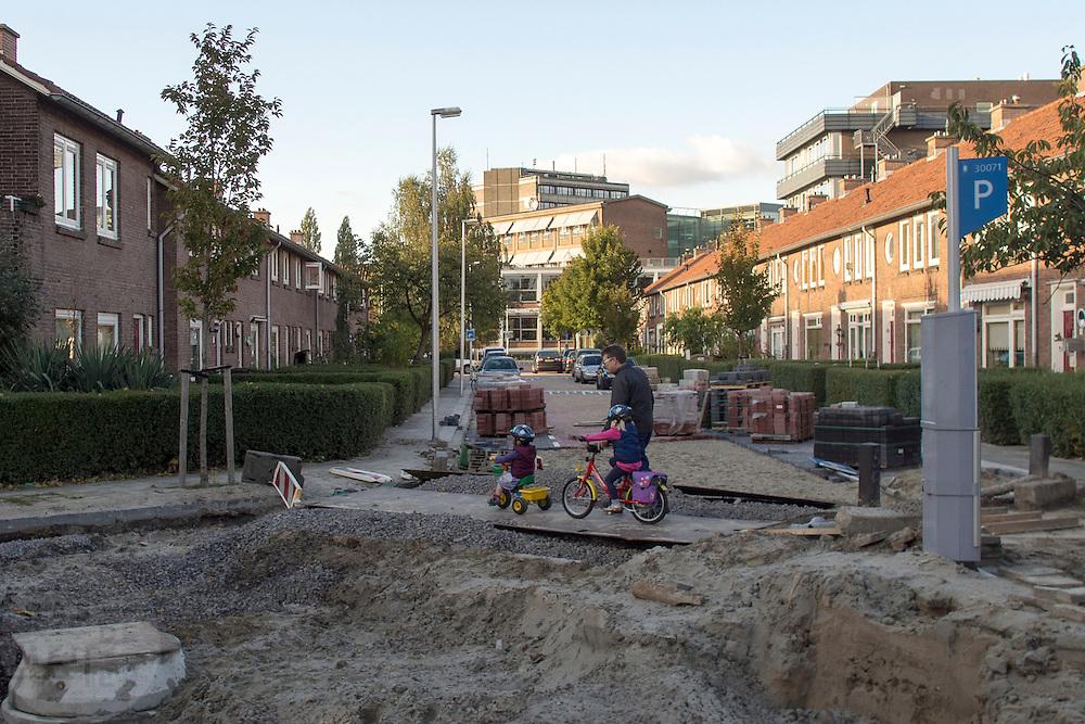 Een man loopt met twee kinderen op kinderfietsen over een opengebroken weg in de Utrechtse wijk Pijlsweerd.<br /> <br /> A man is crossing an open road withtow children on their bike.
