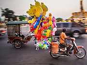 26 FEBRUARY 2015 - PHNOM PENH, CAMBODIA: An inflatable toy vendor rides his motorcycle past the Royal Palace in Phnom Penh.   PHOTO BY JACK KURTZ