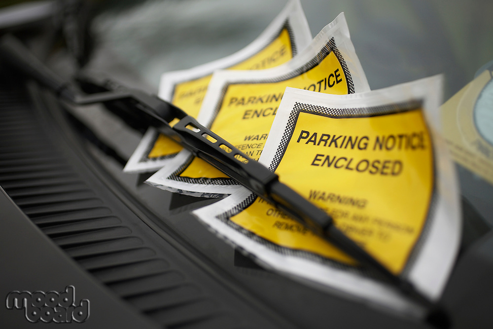 Parking tickets under windshield wiper, close-up