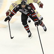 Josh Manson #3 of the Northeastern Huskies keeps the puck from Kevin Hayes #12 of the Boston College Eagles during The Beanpot Championship Game at TD Garden on February 10, 2014 in Boston, Massachusetts. (Photo by Elan Kawesch)