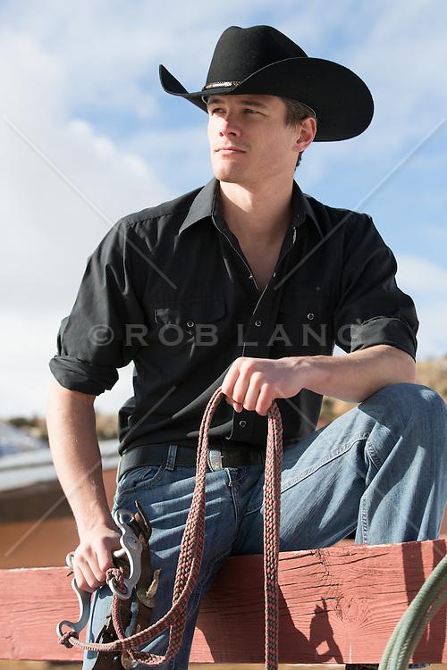 sexy cowboy sitting on a fence on a ranch
