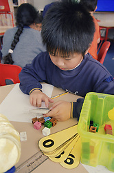 Primary school boy using calculator at desk in practical maths lesson,