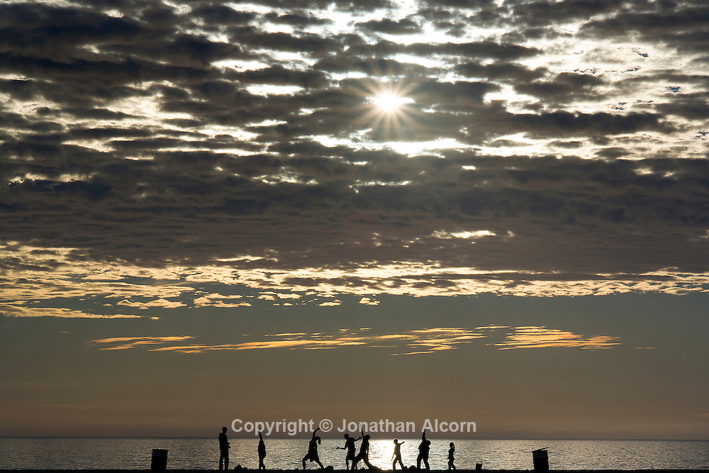 Yoga practice on Santa Monica beach with high clouds in the sky