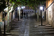 Young men walking on Cuesta de Carvajal cobbled street in Salamanca, Spain