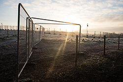 Harefield, UK. 21 January, 2020. The sun rises behind Heras fencing and security cameras on land in the Colne Valley designated for the HS2 high-speed rail link.