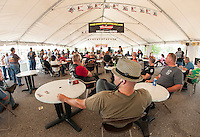 Folks enjoy some blues with Michael Vincent Band and a break from the hot sun under the entertainment tent at Laconia Harley Davidson in Meredith on Thursday afternoon.  (Karen Bobotas/for the Laconia Daily Sun)