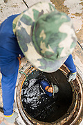 24 AUGUST 2013 - BANGKOK, THAILAND: A prisoner looks up while working in a sewer in Bangkok. A work gang from a prison near Bangkok was cleaning out the sewers along Soi 22 Sukhumvit.      PHOTO BY JACK KURTZ