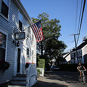 A cyclist in the streets of Nantucket Town Center, Nantucket, Nantucket Island, Massachusetts, USA. Photo Tim Clayton