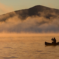 Canoeing in Lily Bay at sunrise, Moosehead Lake, Maine.  Lily Bay Mountian is in the distance. (MR)