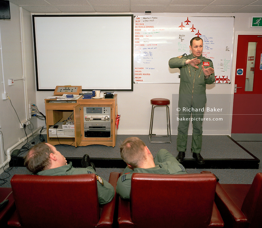 Squadron Leader Spike Jepson, leader of the elite 'Red Arrows', Britain's prestigious Royal Air Force aerobatic team, demonstrates the Corkscrew manoeuvre to his group of pilots and visitors in the briefing room at their RAF Scampton, Lincolnshire headquarters. Using two scaled model Hawk jet aircraft he shows how their formation is to be flown on their next training flight. Five autumn and winter months are spent teaching new recruits manual aerobatic display flying while the older members (who rotate positions) learn new disciplines within the routine. Their leaning curve is steep, even for these accomplished fast-jet aviators who had already accumulated 1,500 hours in fighters. By Summer they need every aspect of their 25-minute displays honed to perfection. In this meeting room they meet before and after every flight discussing safety, merits and failures.