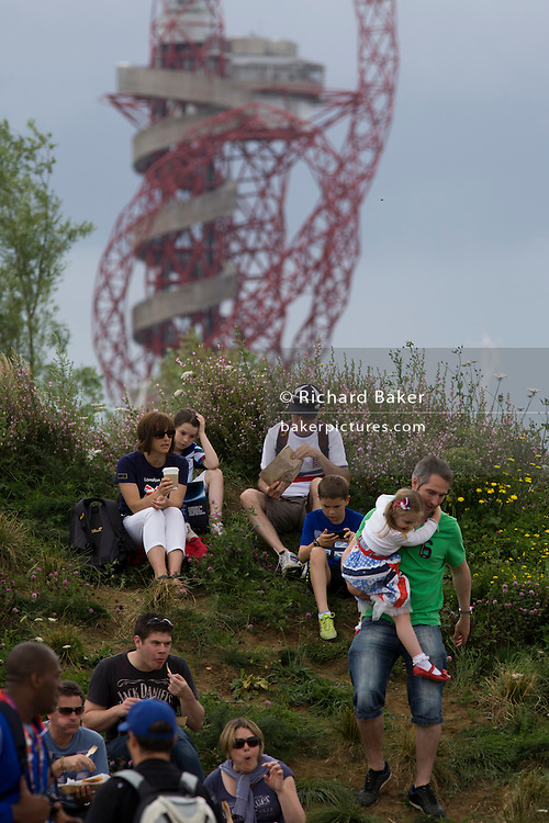 Families climb on to a small hill that has the Orbit artwork tower in the background. during the London 2012 Olympics. Standing 115 metres high, the Orbit is the tallest art structure in Britain - offering views over the Olympic Stadium, Olympic Park and the whole of London. This land was transformed to become a 2.5 Sq Km sporting complex, once industrial businesses and now the venue of eight venues including the main arena, Aquatics Centre and Velodrome plus the athletes' Olympic Village. After the Olympics, the park is to be known as Queen Elizabeth Olympic Park.
