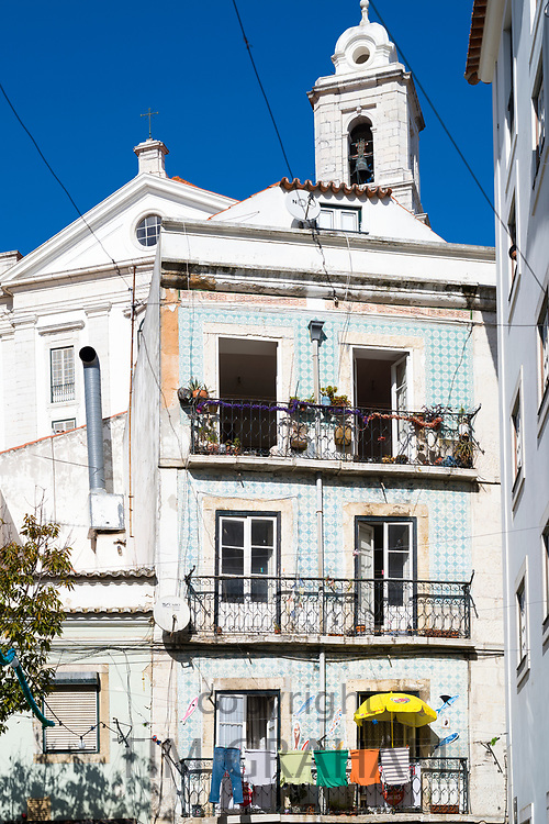 Typical Portugese street scene with laundry hanging out to dry on washing lines on balcony in Lisbon, Portugal