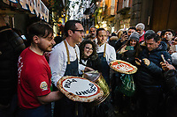 "NAPLES, ITALY - 8 DECEMBER 2017: Gino Sorbillo (39, center), a Master Pizzaiuolo (pizza chef) and owner of Pizzeria Gino Sorbillo,  together with his brother Toto (right) and a pizzaiuolo (left) pose for pictures and selfies with a customers and pedestrians as they hold commemorative pizzas to celebrate the art of Pizzaiuolo added to Unesco's list of Intangible Cultural Heritage of Humanity, here by his pizzeria in Naples, Italy, on December 8th 2017.<br /> <br /> On Thursday December 7th 2017, UNESCO added the art of Neapolitan ""Pizzaiuolo"" to its list of Intangible Cultural Heritage of Humanity.<br /> <br /> The art of the Neapolitan 'Pizzaiuolo' is a culinary practice comprising four different phases relating to the preparation of the dough and its baking in a wood-fired oven, involving a rotatory movement by the baker. The element originates in Naples, the capital of the Campania Region, where about 3,000 Pizzaiuoli now live and perform. Pizzaiuoli are a living link for the communities concerned. There are three primary categories of bearers – the Master Pizzaiuolo, the Pizzaiuolo and the baker – as well as the families in Naples who reproduce the art in their own homes. The element fosters social gatherings and intergenerational exchange, and assumes a character of the spectacular, with the Pizzaiuolo at the centre of their 'bottega' sharing their art.<br /> <br /> In Naples, pizza makers celebrated the victory by giving away free pizzas."