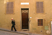 An old Italian man walks past door number 19 where Gallileo the mathematician lived on Costa di San Giorgio, Florence, Tuscany, Italy.