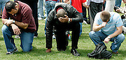 Men prey for the victims shot in the Virginia Tech tragedy during a group multi-denominational prayer meeting on the campus in Blacksburg, Virginia April 18, 2007.  REUTERS/Rick Wilking (UNITED STATES)