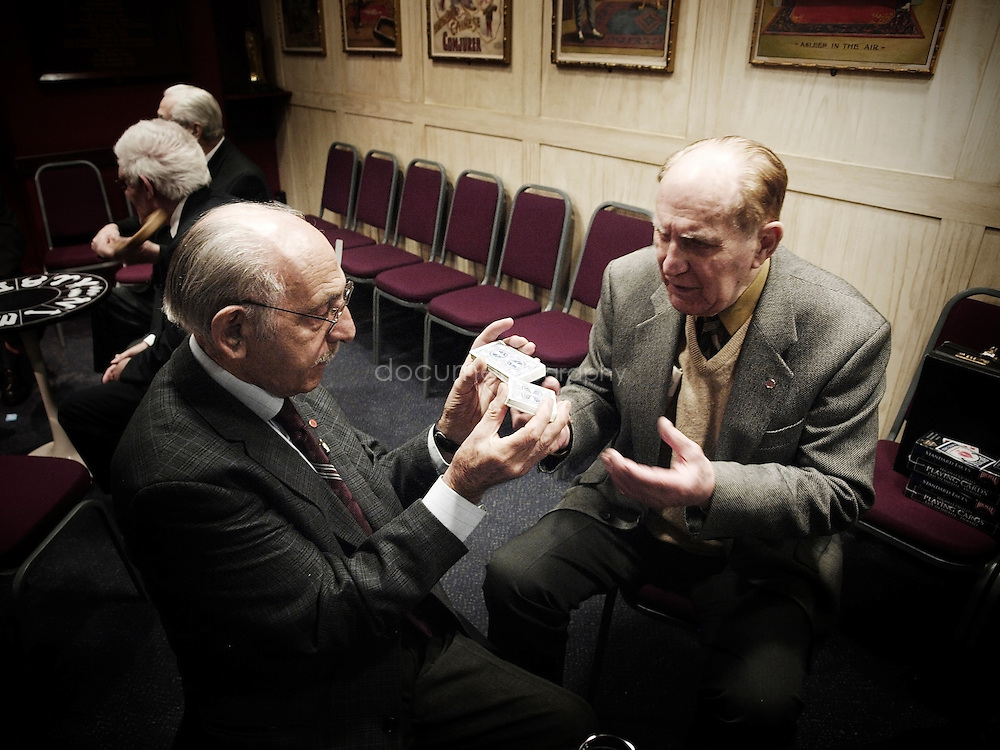 Honorary Vice President Henry Lewis shows a special card shuffle to a fellow member.