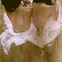Two young women sitting together with bare backs