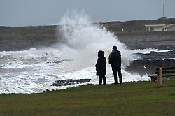 © Licensed to London News Pictures. 03/02/2017. Porthcawl, Mid Glamorgan, Wales, UK. People watch huge waves hit the coastline of the South Wales resort of Porthcawl in Mid Glamorgan, Wales, UK. Photo credit: Graham M. Lawrence/LNP