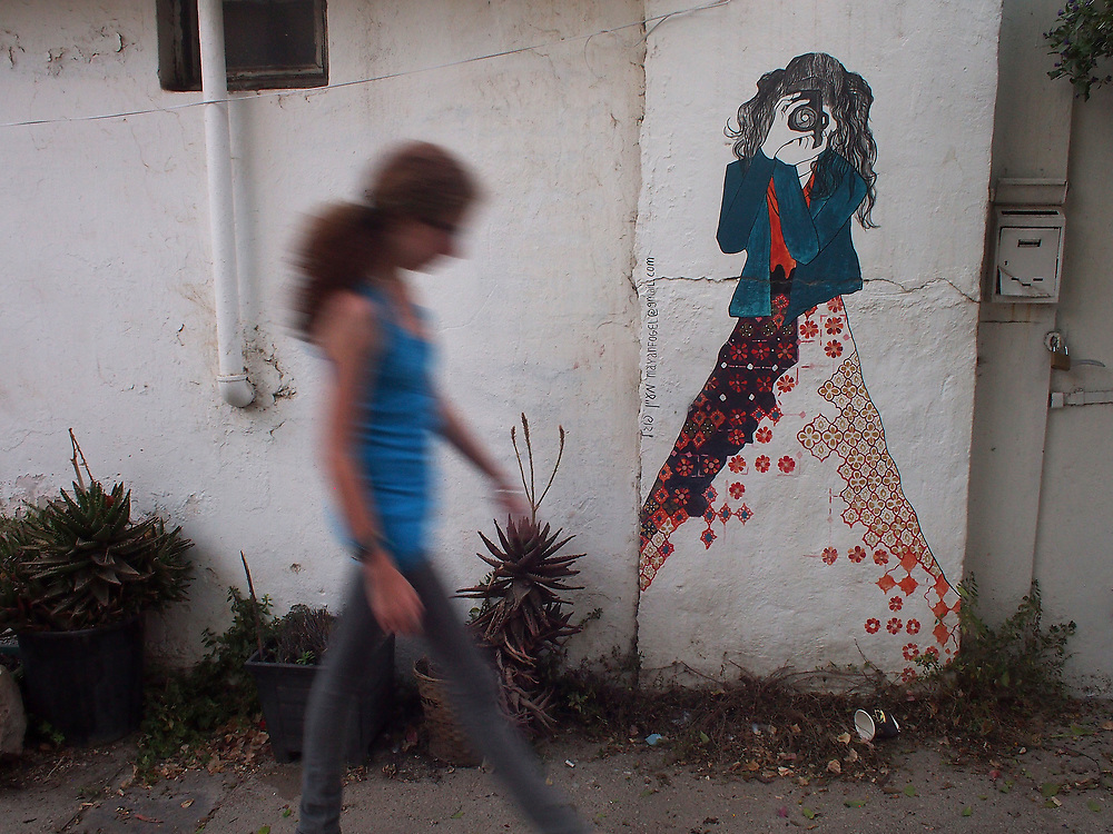 A girl walks in front of a street art painting of a girl taking a photograph in Jerusalem.