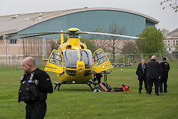 © Licensed to London News Pictures . 20/04/2014 . Manchester , UK . The North West Air Ambulance lands on grass in Platt Fields Park in Manchester , adjacent to an Easter fun fair. A teenaged girl was struck by an 80 year old driver who fell ill behind the wheel of his car , on Chapeltown Road , in Bolton today (Sunday 20th April 2014) . The girl was transported via Air Ambulance to a ground ambulance and on to Manchester Royal Infirmary. She is reported to have suffered head injuries . Both she and the 80 year old driver (who is believed to have suffered a heart attack behind the wheel) are described as being in a serious but stable condition . Photo credit : Joel Goodman/LNP