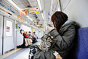 A young woman applies makeup on a train in Tokyo, Japan. The Japanese are well known for their civility and politeness,  but a recent governmental campaign to clamp down on lewd behavior  that may inconvenience others -- including talking on cell phones and applying makeup while commuting on a train -- was fueled by a decline in etiquette and manners.