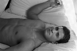 shirtless man face up in bed