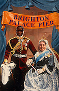 A couple of mixed-race have put their heads through the apertures made in a painting that depicts Prince Albert and Queen Victoria, on the Palace Pier at Brighton, on the south coast of England. The faces peep through this traditional attraction that few can resist, even in the 21st century. The man's face looks disturbingly incongruous in the place where the Prince Consort's white German character would be. There is a message here of a changing multi-cultural British society where these friends or partners are from other ethnic backgrounds and where mixed-marriages are now commonplace, as opposed to the Victorian era when attitudes to racism and race-relations were vastly different.
